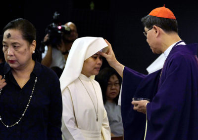 Cardinal Luis Antonio Tagle places ashes on the head of a woman during the Ash Wednesday Mass at the Manila archdiocese chapel in Intramuros, Manila, March 1, 2017.  ROY LAGARDE