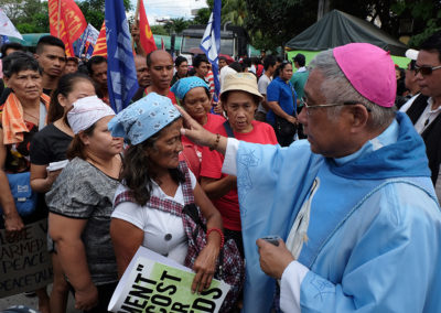An anti-mining protester receives a cross of black ashes on her forehead from Lipa Archbishop Ramon Arguelles outside the Senate building in Manila on Ash Wednesday, March 1, 2017. ROY LAGARDE